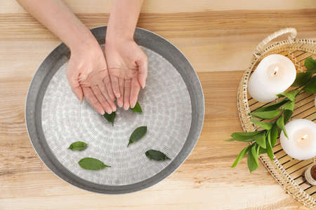 Woman soaking her hands in bowl with water and leaves on wooden table, top view. Spa treatment 版權商用圖片