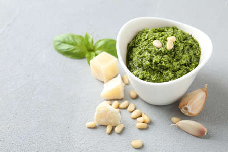 Composition with bowl of tasty pesto sauce on grey table. Space for text Stok Fotoğraf