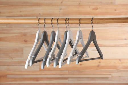 Rack with clothes hangers on wooden background Banco de Imagens