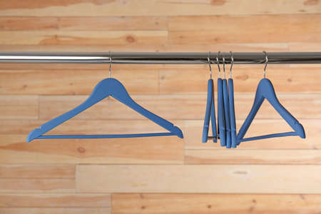Metal rack with clothes hangers on wooden background Banco de Imagens