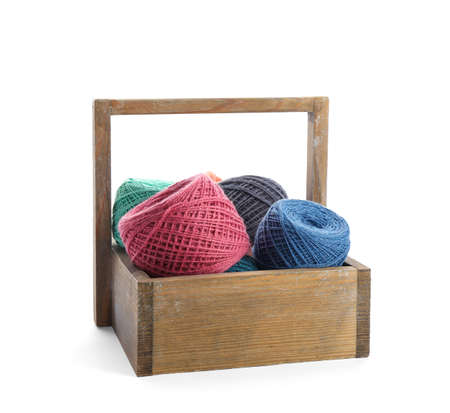 Wooden basket with clews of colorful knitting threads on white background