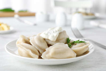 Plate of tasty dumplings served with sour cream and dill on table