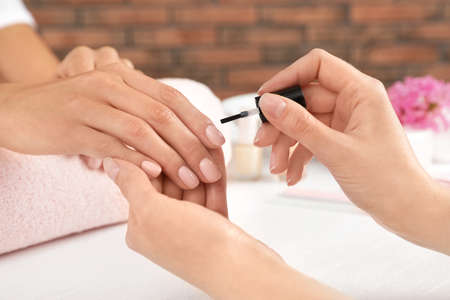 Manicurist applying polish on clients nails at table, closeup. Spa treatment