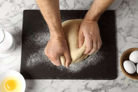 Male baker preparing bread dough at kitchen table, top view 写真素材