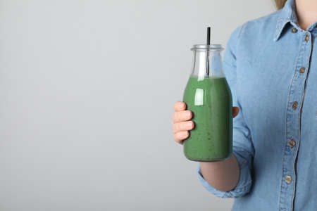 Woman holding bottle with spirulina smoothie on grey background, closeup. Space for text Banco de Imagens