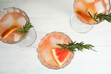Glasses of grapefruit cocktails on white table, flat lay Stok Fotoğraf
