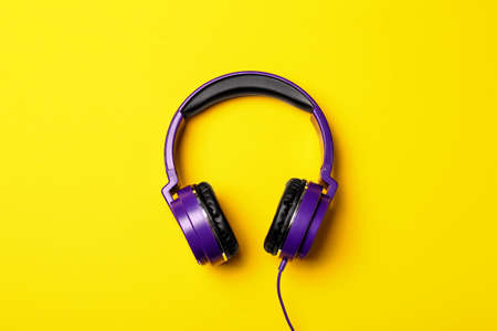 Stylish modern headphones on color background, top view