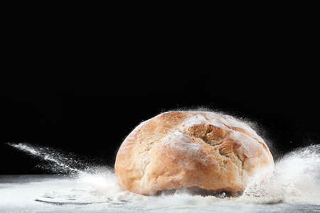 Baker and loaf of bread on table against dark background. Space for text