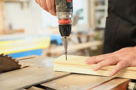 Working man using electric screwdriver at carpentry shop, closeup