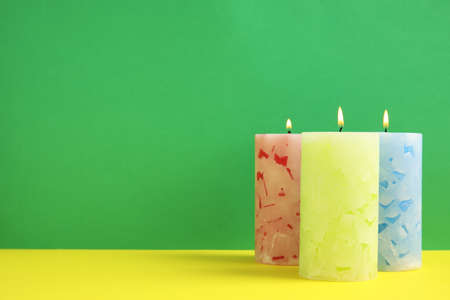 Alight wax candles on color background. Space for text Imagens - 124992171