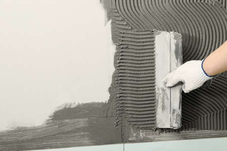 Closeup of worker spreading concrete on wall with spatula, space for text. Tile installation Banco de Imagens