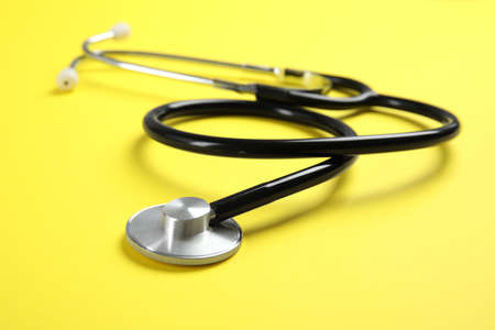 Stethoscope on color background, closeup. Medical tool