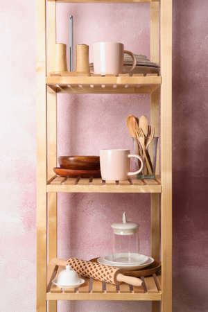 Wooden shelving unit with set of kitchenware near color wall