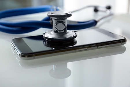 Smartphone and stethoscope on light table, closeup. Repairing service