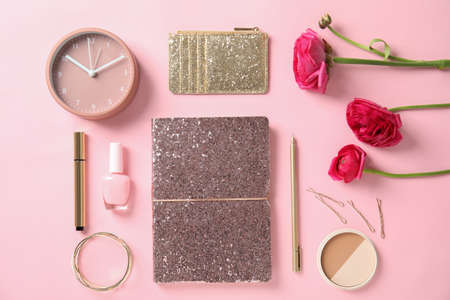 Flat lay composition with glittering notebook, cosmetics and spring flowers on color background Stock Photo