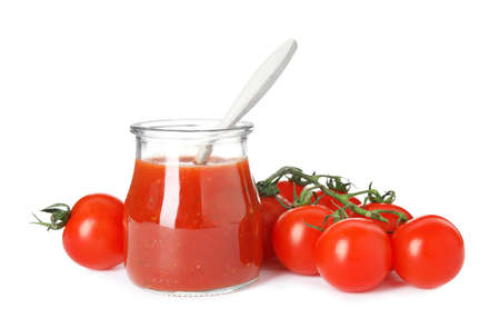 Jar of sauce with spoon and tomatoes isolated on white