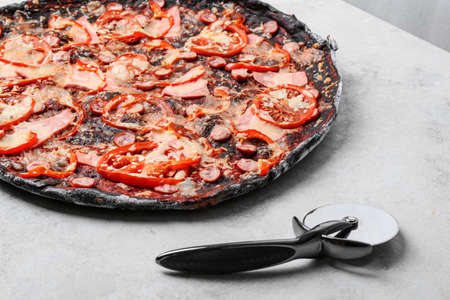 Black pizza and knife on grey table, closeup