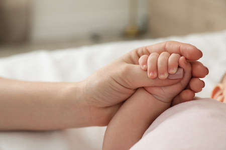 Mother holding babys hand on blurred background, closeup