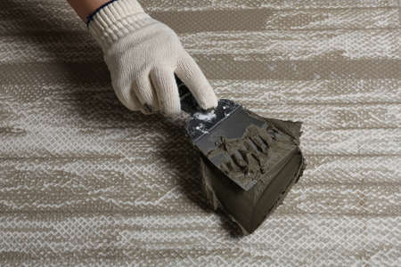 Worker spreading concrete on ceramic tile with spatula, closeup