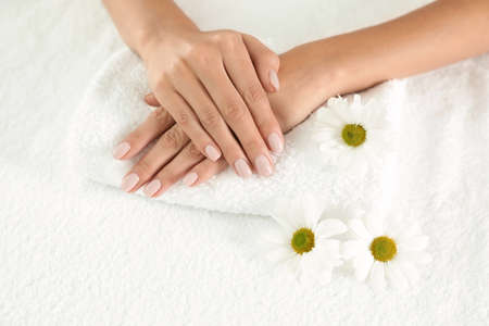 Woman with smooth hands and flowers on towel, closeup. Spa treatment