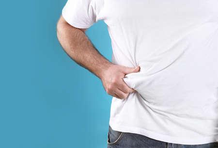 Uomo sovrappeso con grande pancia su sfondo colorato, primo piano