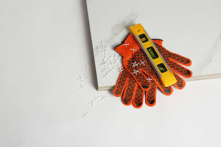 Composition with ceramic tiles and gloves on white background, top view 写真素材 - 124997390