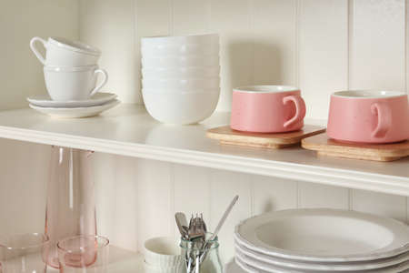 White shelving unit with set of dishware