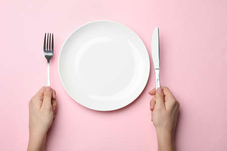 Woman with fork, knife and empty plate on color background, top view Stock Photo