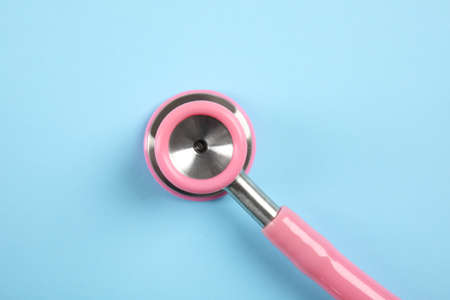 Stethoscope on color background, top view. Medical tool