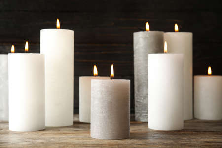 Many alight wax candles on table against dark background 版權商用圖片