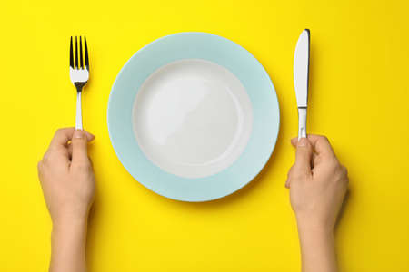 Woman with fork, knife and empty plate on color background, top view Stockfoto