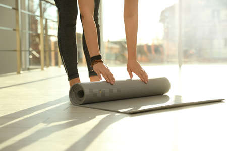 Young woman rolling yoga mat in sunlit room, closeup