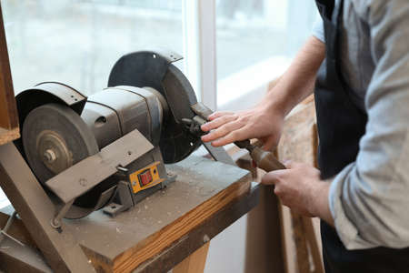Working man using grinding machine at carpentry shop, closeup
