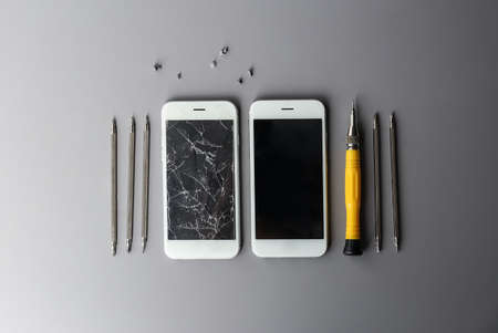 Flat lay composition with mobile phones and tools on grey background, space for text. Repairing service Stock Photo