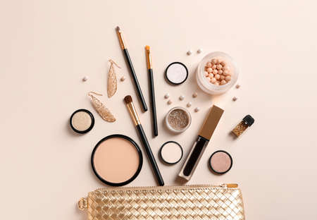 Cosmetic bag and different luxury makeup products on color background, flat lay
