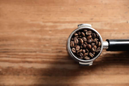 Portafilter with roasted coffee beans on wooden table, top view. Space for text