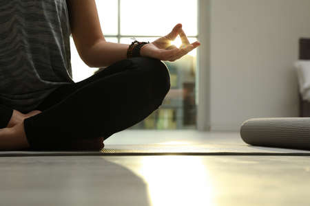 Young woman practicing yoga in sunlit room, closeup with space for text Stockfoto
