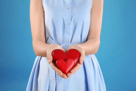 Woman holding decorative hearts on color background, closeup Imagens