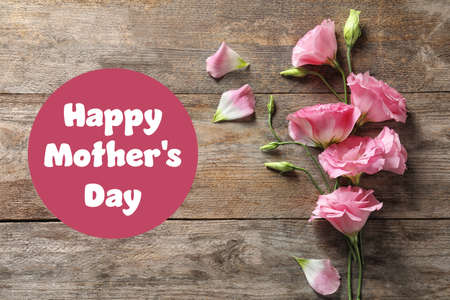 Beautiful eustoma flowers and text Happy Mothers Day on wooden background, top view 스톡 콘텐츠