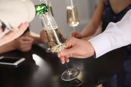 Waiter pouring champagne into mans glass at party, closeup Stock Photo