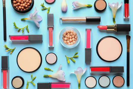Makeup products and flowers on color background, flat lay