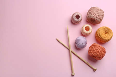 Clews of threads and knitting needles on color background, flat lay. Sewing stuff