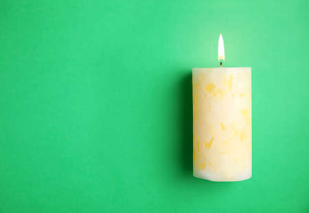 Alight wax candle and space for text on color background Stock Photo