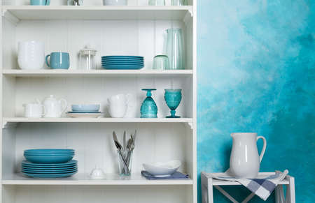White shelving unit with set of dishware near color wall
