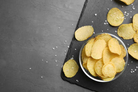 Slate board with potato chips on grey table, flat lay. Space for text Imagens - 124957605
