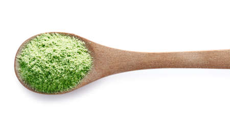 Wheat grass powder in wooden spoon on white background, top view