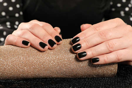 Woman showing black manicure on rolled shiny paper, closeup. Nail polish trends