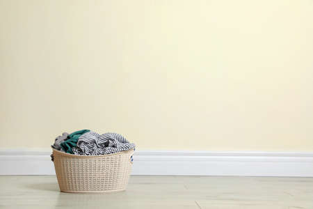 Plastic laundry basket full of dirty clothes on floor near color wall. Space for text Imagens - 124957641