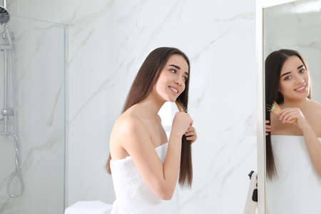 Beautiful young woman with hair brush looking into mirror in bathroom Reklamní fotografie