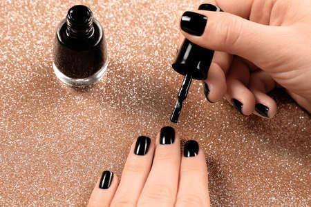 Woman applying black nail polish on shiny color background, closeup